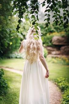 Braut mit langen blonden haaren von hinten im garten