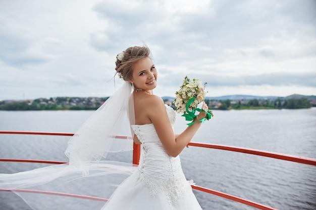 Braut mit langen haarblumen in ihren händen, die im wind stehen