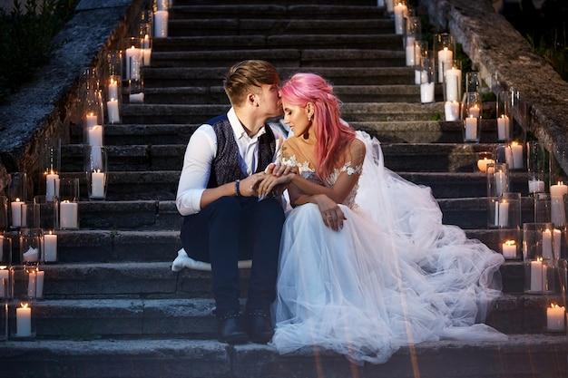 Braut mit rosa haaren und stilvollen bräutigam sitzen auf den spuren mit glänzenden kerzen