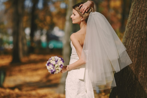Braut mit schleier und blumenstrauß