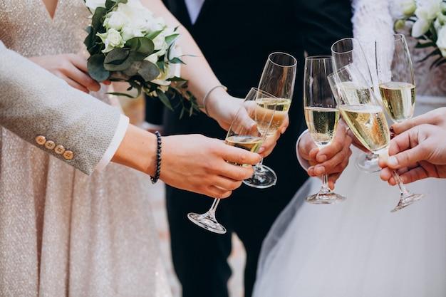 Braut mit trinkendem champaigne des bräutigams auf ihrer hochzeit