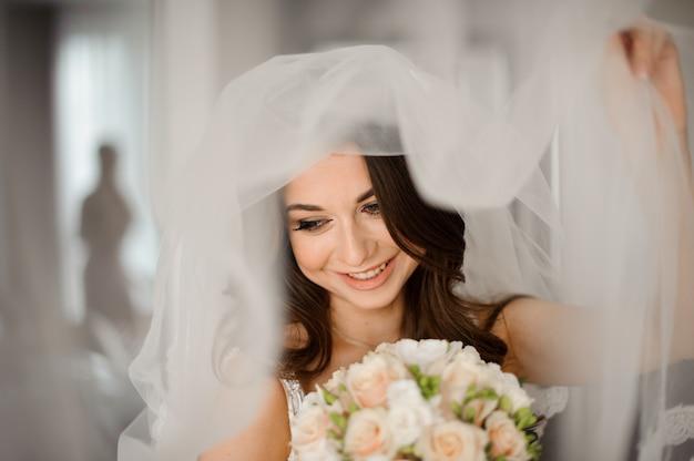 Braut morgen vorbereitung. attraktive und lächelnde braut in einem weißen schleier mit einem hochzeitsblumenstrauß