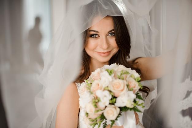 Braut morgen vorbereitung. glückliche und lächelnde braut in einem weißen schleier mit einem hochzeitsblumenstrauß