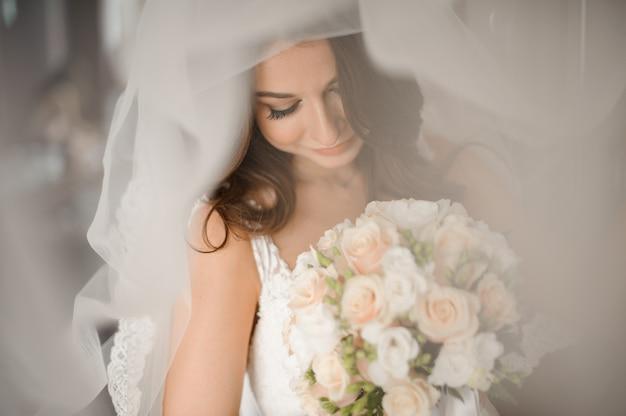 Braut morgen vorbereitung. reizende braut in einem weißen schleier mit einem hochzeitsblumenstrauß