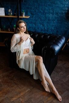 Braut morgen vorbereitung. schöne junge frau im weißen hochzeitsnegligé hat spaß in einem dunklen studio