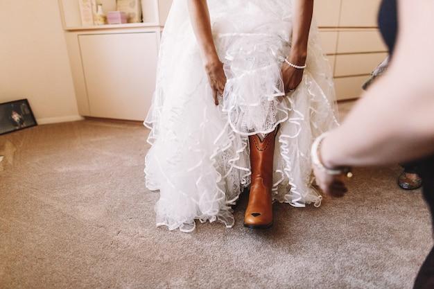 Braut passt roten stiefel auf ihr bein an