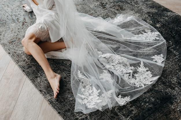 Braut sitzt auf dem boden auf teppich und trägt einen langen spitzenschleier.