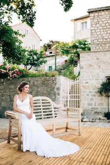 Braut sitzt auf einer holzbank in einem gemütlichen innenhof in der nähe von weißen backsteinhäusern perast