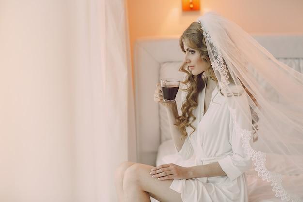 Braut sitzt mit einer tasse