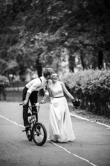 Braut springt auf das fahrrad. die braut drehte sich um, um sich anzuziehen. lächeln. schwarzweiss-foto. im romantischen europäischen park