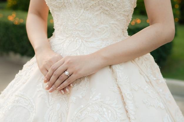 Braut stehend und handhaltung mit ehering. hochzeits- und schönheitskonzept.