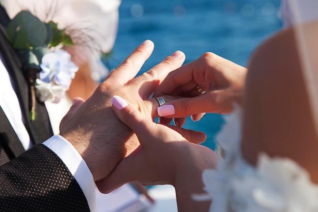 Braut trägt ehering, um auf hintergrund des meeres zu pflegen