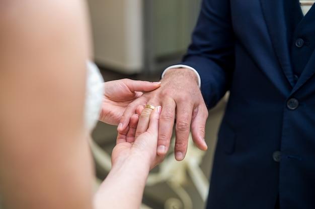 Braut trägt einen ehering am bräutigam.