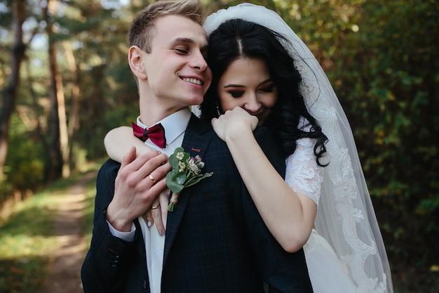Braut umarmt bräutigam stehend im wald