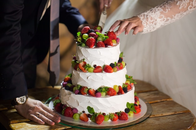 Braut und bräutigam am hochzeitsempfang schneiden der hochzeitstorte
