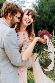 Braut und bräutigam am hochzeitstag, der draußen auf frühlingsnatur geht. glückliche frisch verheiratete frau und mann, die im grünen park umarmen. liebevolles hochzeitspaar.