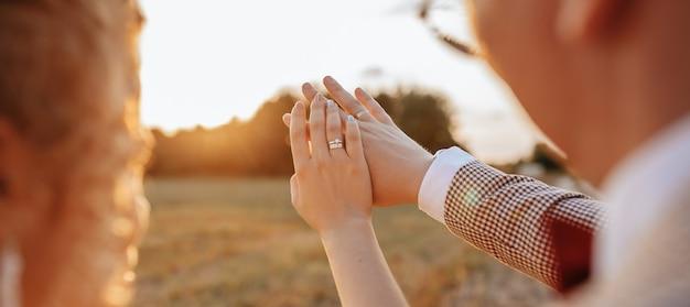 Braut und bräutigam am hochzeitstag umarmen und sehen ringe bei sonnenuntergang