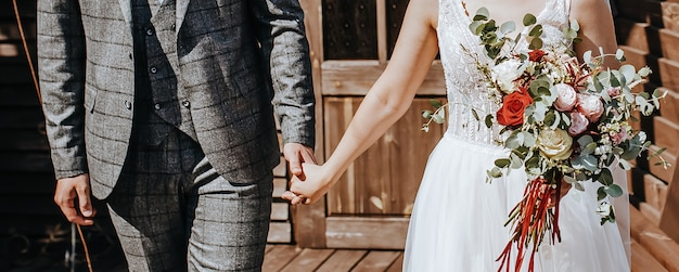 Braut und bräutigam am hochzeitstag umarmen und zeigen liebe mit einem hochzeitsstrauß aus rosenblüten