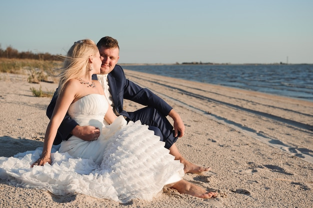 Braut und bräutigam am meer an ihrem hochzeitstag.