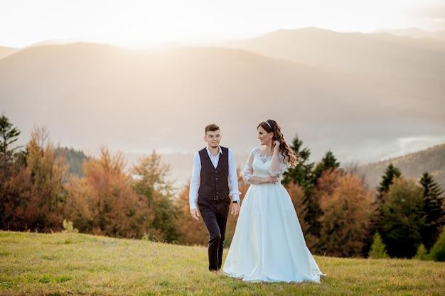 Braut und bräutigam am sonnenuntergang-romantischen verheirateten paar