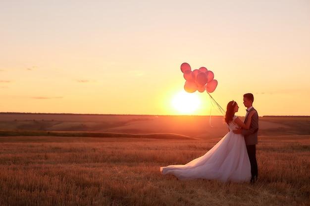 Braut und bräutigam auf einem gebiet bei sonnenuntergang mit ballon.