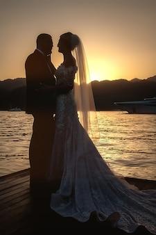 Braut und bräutigam auf meer oder meer bei sonnenuntergang am hochzeitstag. silhouette der braut im hochzeitskleid (kleid und schleier) vor dem hintergrund der sonne hinter den bergen. ende des hochzeitstages