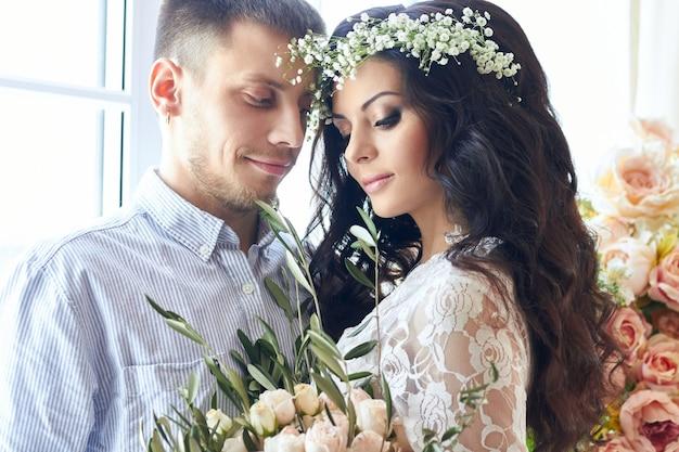 Braut und bräutigam bereiten sich morgens auf die hochzeit vor. liebespaar, das sich zu hause umarmt. hübscher bräutigam und charmante braut. paar macht sich bereit hochzeitszeremonie