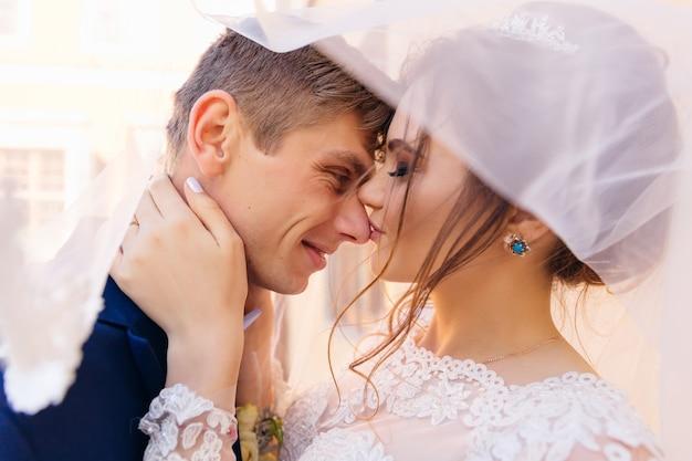 Braut und bräutigam berühren sich die nase, schließen die augen und lächeln unter dem hochzeitsschleier aus nächster nähe