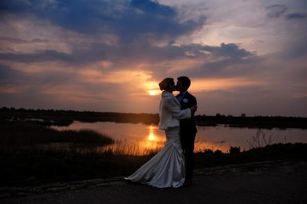 Braut und bräutigam, die am schönen romantischen verheirateten paar des sonnenuntergangs küssen