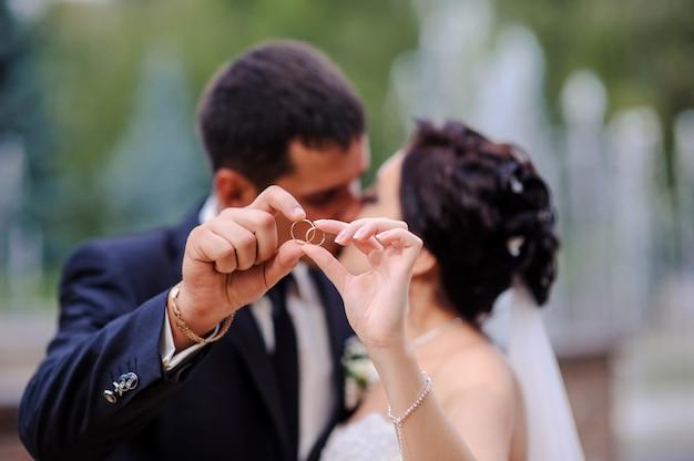 Braut und bräutigam, die den ring im vordergrund halten