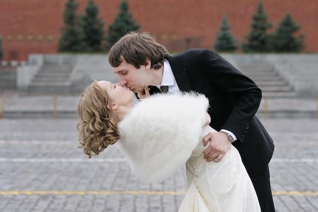 Braut und bräutigam, die draußen küssen