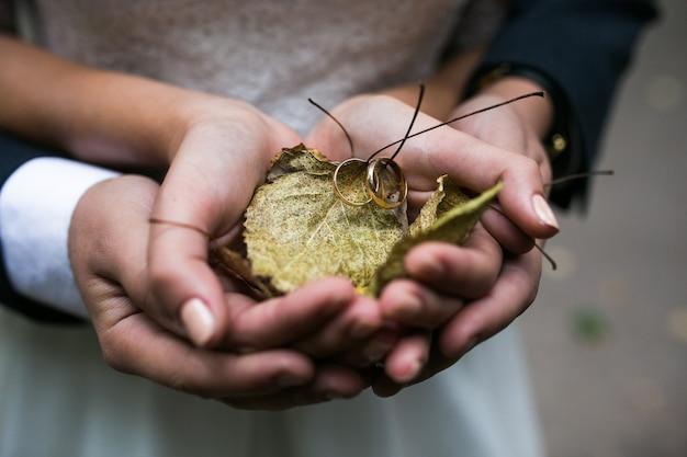 Braut und bräutigam, die eheringe und herbstlaub in den händen halten