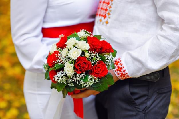 Braut und bräutigam, die einen blumenstrauß der roten hochzeit halten