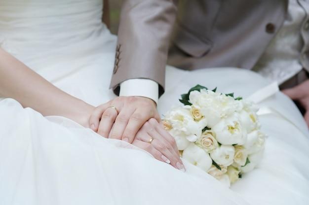 Braut und bräutigam die hände mit eheringen