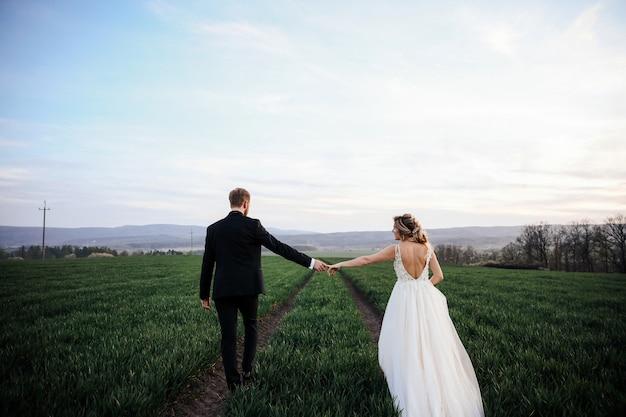 Braut und bräutigam, die ihre hände halten, gehen über den weg nach draußen