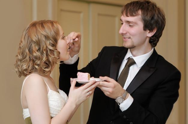 Braut und bräutigam, die ihre süße hochzeitstorte essen