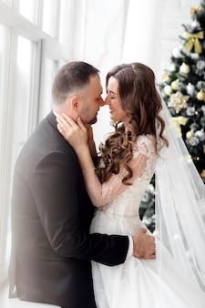 Braut und bräutigam, die im studio auf hintergrund aufwerfen, der mit weihnachtsbaum in ihrem hochzeitstag verziert wird