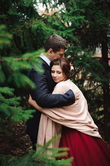 Braut und bräutigam, die in einem wald im herbstwald umarmen