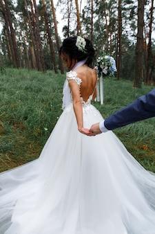Braut und bräutigam, die in grüne parkrückseitenansicht gehen. jungvermählten im freienhändchenhalten am sonnigen tag. hochzeitstag. hochzeitspaare, die romantische momente genießen