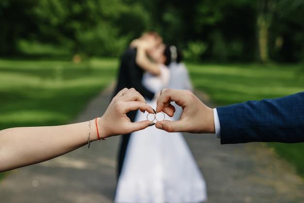 Braut und bräutigam, die zwei eheringe nah an einander halten