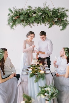 Braut und bräutigam essen die mit kiefern, beeren und baumwollblumen verzierte hochzeitstorte mit ihren brautjungfern und trauzeugen