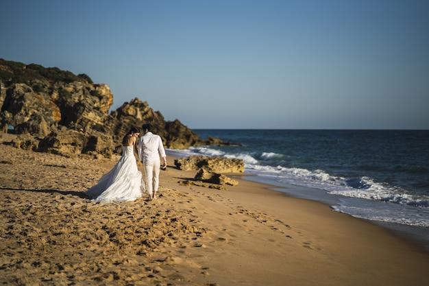Braut und bräutigam gehen am sandstrand spazieren