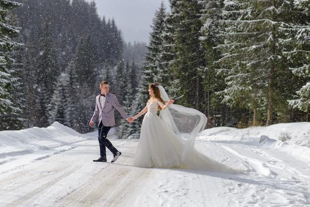 Braut und bräutigam gehen an der hand vor dem hintergrund eines winterwaldes. es schneit.