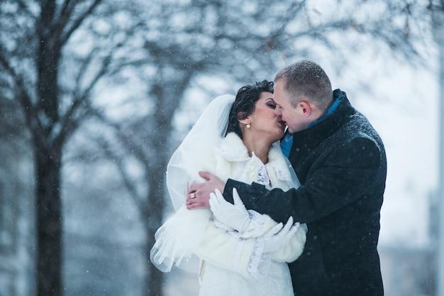 Braut und bräutigam gehen auf der europäischen stadt im schnee
