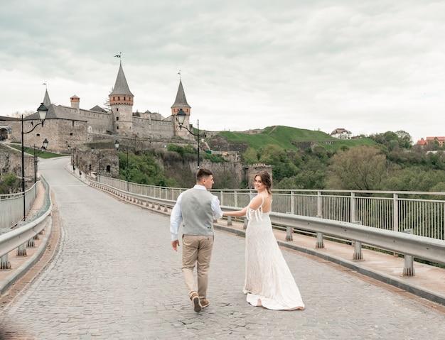 Braut und bräutigam gehen bei der hochzeitszeremonie durch das alte schloss