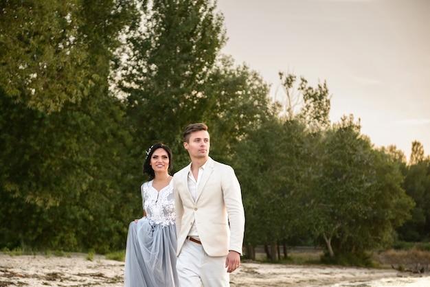 Braut und bräutigam gehen bei sonnenuntergang