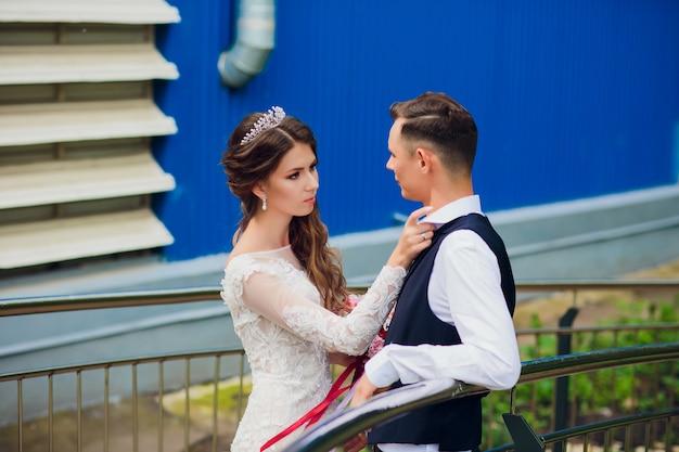 Braut und bräutigam gehen in der stadt, hochzeitstag, ehekonzept. braut und bräutigam im städtischen hintergrund. junges paar, das am hochzeitstag auf einer treppe geht.