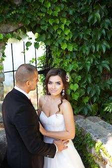 Braut und bräutigam gehen um gebäude herum. hochzeitstag.