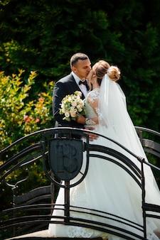 Braut und bräutigam gehen zusammen im park spazieren. charmante braut in einem weißen kleid, der bräutigam trägt einen dunklen, eleganten anzug.