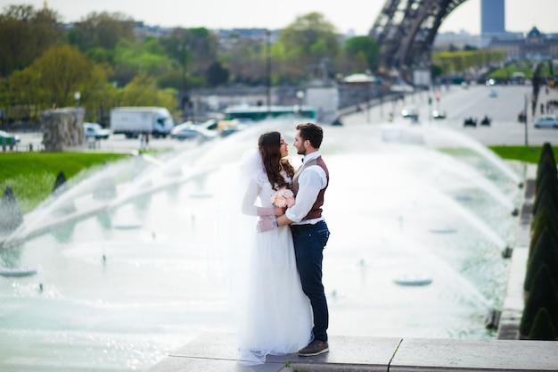 Braut und bräutigam haben einen romantischen moment an ihrem hochzeitstag in paris vor der eiffeltour